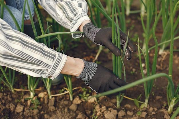 Femme au chapeau travaillant dans un jardin