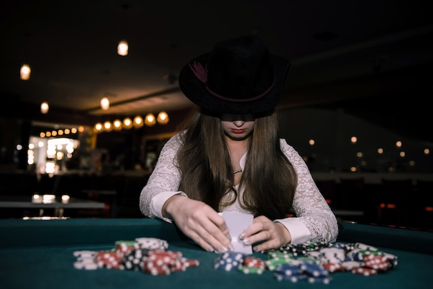 Femme au chapeau vérifiant ses cartes au casino