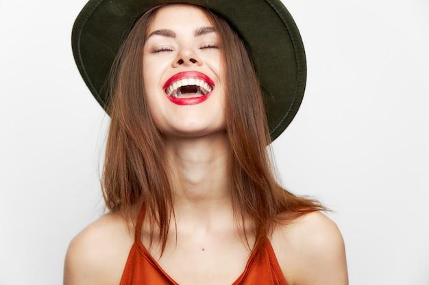 Femme au chapeau vert le charme sourit largement avec le maquillage du soir les yeux fermés