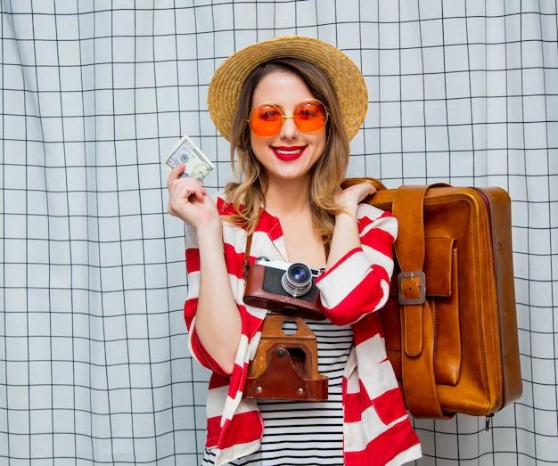 Femme au chapeau et veste rayée avec appareil photo vintage, valise et billets