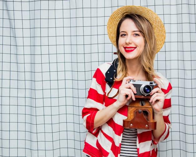 Femme au chapeau et veste rayée avec appareil photo vintage