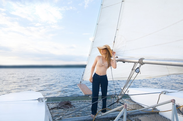 Une femme au chapeau sur un yacht, contre le ciel et la mer.