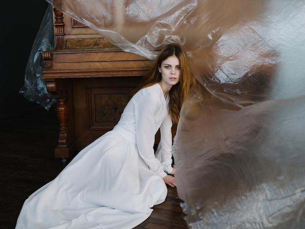 Femme au charme de la robe blanche posant l'intérieur du piano. photo de haute qualité