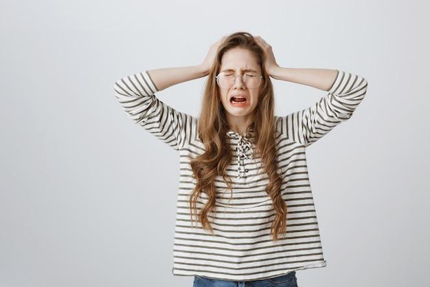 Femme au cœur brisé et en détresse pleurer, tenant les mains sur la tête triste