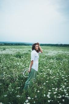 Une femme au coucher du soleil parcourt le champ de marguerites