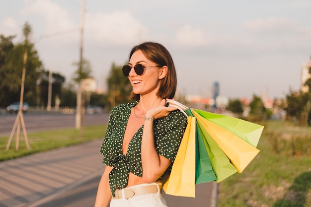 Femme au coucher du soleil avec des sacs colorés au parc de la rue de la ville après une journée de shopping heureuse