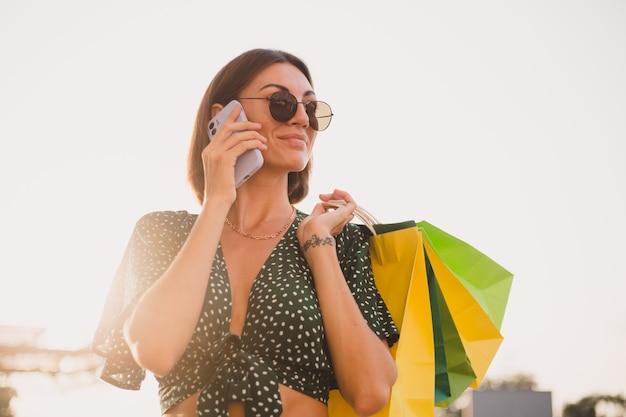 Femme au coucher du soleil avec des sacs à provisions colorés et un parking près du centre commercial heureux avec un téléphone portable