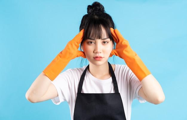 Femme au foyer asiatique porte des gants orange et tient un jet d'eau dans sa main