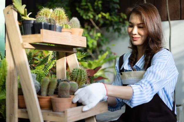 Femme au foyer asiatique en tablier assis et arrangeant des pots de cactus comme passe-temps dans la maison.