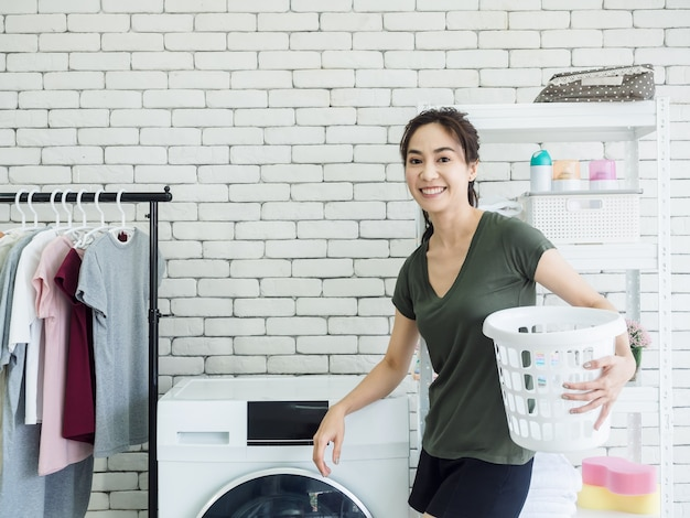 Femme au foyer de belle jeune femme asiatique debout et tenant le panier de tissu blanc vide avec souriant près de machine à laver dans la buanderie.