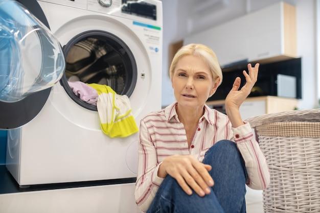 Femme au foyer blonde en chemise rayée assis près de la machine à laver
