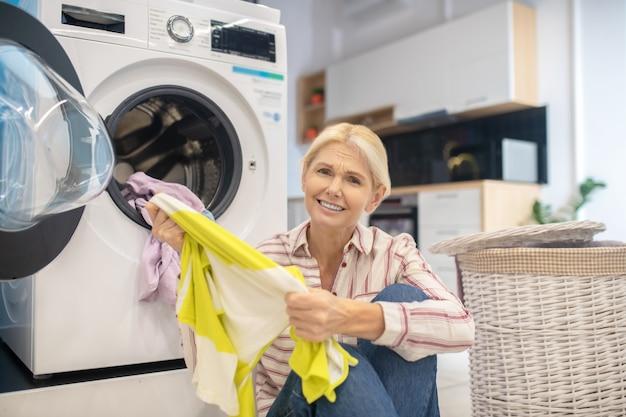 Femme au foyer blonde en chemise rayée et jeans assis près de la machine à laver