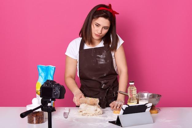 Femme au foyer brune travaillant dur, essayant une nouvelle recette