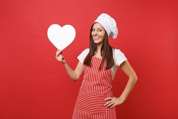 Femme au foyer chef cuisinier ou boulanger en tablier rayé, t-shirt blanc, chapeau de chef toque isolé sur fond de mur rouge. femme de ménage souriante tenir un espace de travail coeur vide. maquette du concept d'espace de copie.