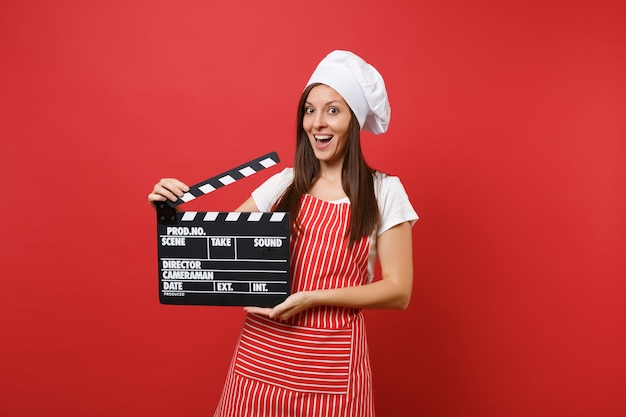 Femme Au Foyer Chef Cuisinier Ou Boulanger En Tablier Rayé, T-shirt Blanc, Chapeau De Chef Toque Isolé Sur Fond De Mur Rouge. Femme Tenant Un Film Noir Classique En Clap. Maquette Du Concept D'espace De Copie. Photo Premium