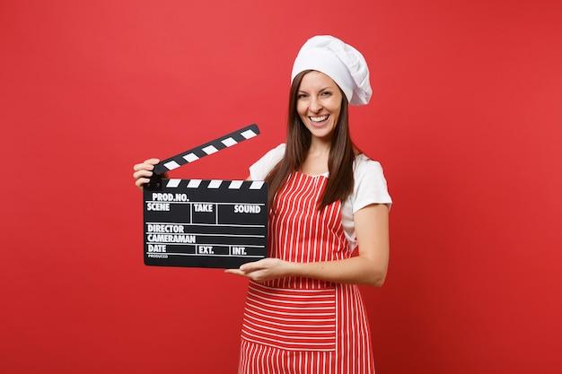Femme au foyer chef cuisinier ou boulanger en tablier rayé, t-shirt blanc, chapeau de chef toque isolé sur fond de mur rouge. femme tenant un film noir classique en clap. maquette du concept d'espace de copie.