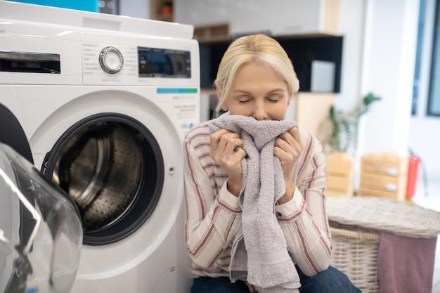 Femme au foyer en chemise rayée assis près de la machine à laver et tenant des vêtements propres dans les mains