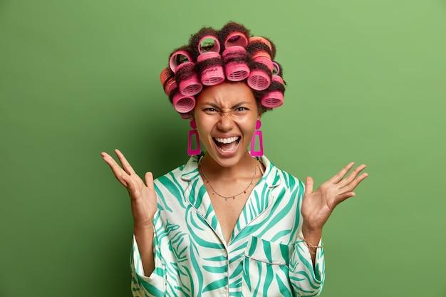 La femme au foyer en colère folle fait des gestes avec agacement, crie après son mari ou ses enfants, exprime de l'irritation, se sent malade et fatiguée du travail domestique, demande du temps pour elle-même, fait une coiffure, porte des bigoudis