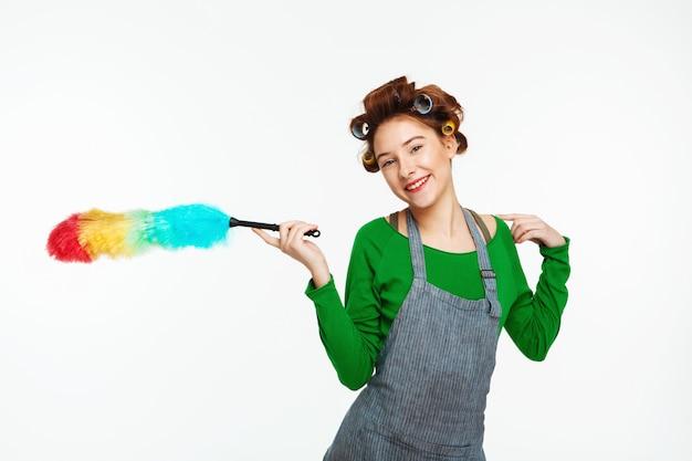 Femme au foyer cool sourit tenant plumeau dans les mains