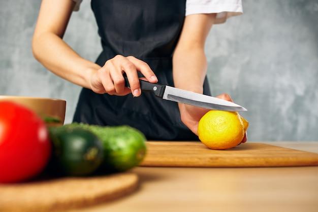 Femme au foyer sur la cuisine coupant des légumes