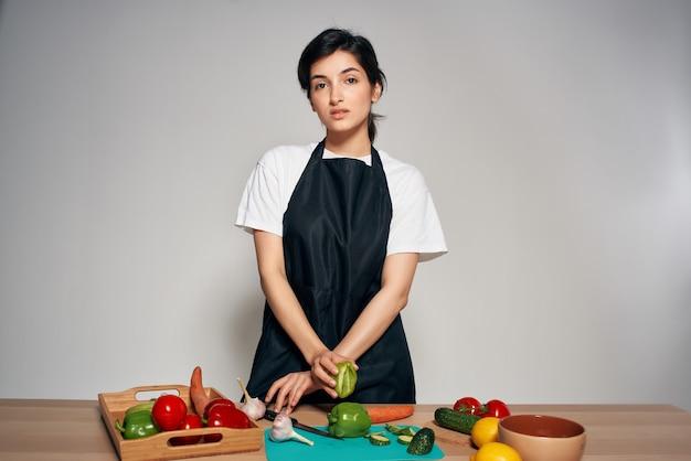 Femme au foyer dans un tablier noir dans la cuisine aliments sains légumes frais