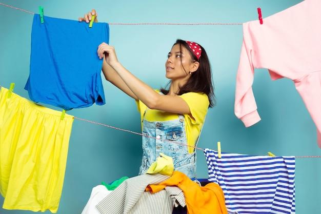Femme au foyer drôle et belle faire des travaux ménagers isolés sur l'espace bleu