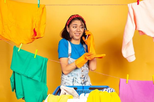 Femme au foyer drôle et belle faire des travaux ménagers isolés sur l'espace jaune. jeune femme caucasienne entourée de vêtements lavés