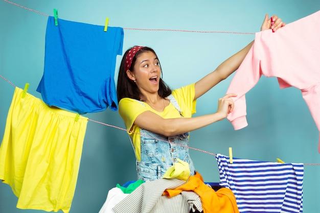 Femme au foyer drôle et belle faire des travaux ménagers isolés sur fond bleu. jeune femme caucasienne entourée de vêtements lavés. vie domestique, œuvres d'art lumineuses, concept d'entretien ménager. plier le linge.