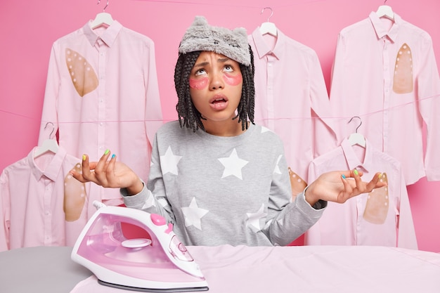 Une femme au foyer du millénaire, malheureuse et frustrée, écarte les paumes de ses mains et en a marre de faire des tâches ménagères près d'une planche à repasser applique des patchs de beauté sous les yeux, porte un masque de sommeil et un pyjama