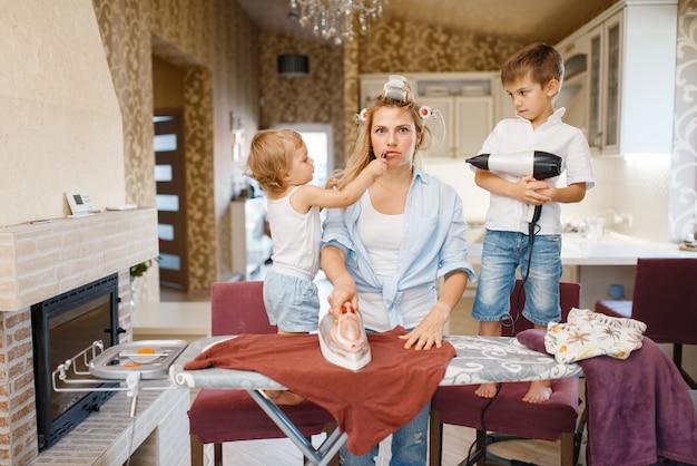Femme au foyer et enfants jouant avec un sèche-cheveux