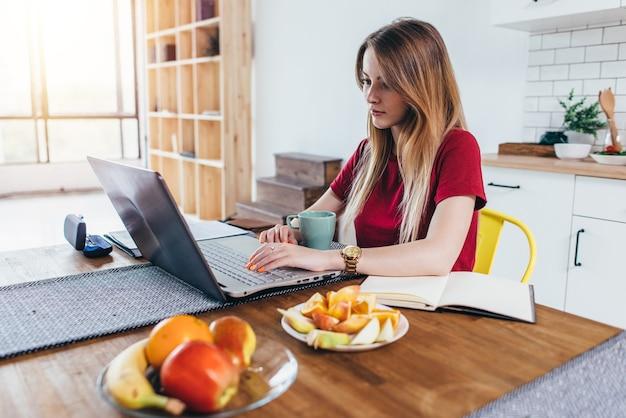 Femme au foyer est assise à la table de la cuisine avec un ordinateur portable.