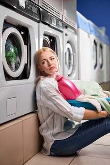 Femme au foyer fatiguée de 20 ans portant un panier à linge avec des vêtements sales en attente de fin de lavage, assise sur le sol de mauvaise humeur, épuisée. dans la maison de lavage