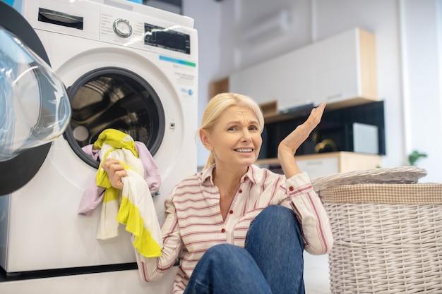 Femme au foyer. femme au foyer blonde en chemise rayée assis près de la machine à laver