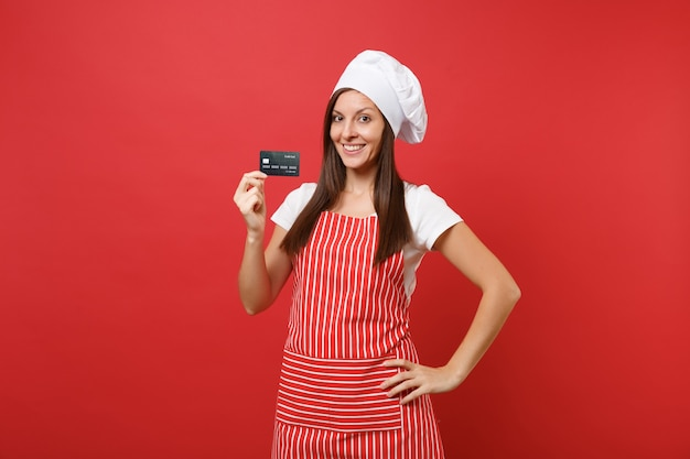 Femme au foyer femme chef cuisinier boulanger en tablier rayé blanc t-shirt toque chapeau de chefs isolé sur fond de mur rouge. une femme souriante tient en main une carte bancaire de crédit, de l'argent sans numéraire. maquette concept d'espace de copie