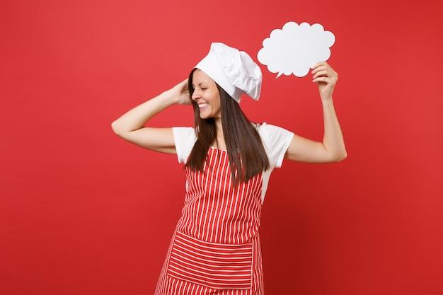 Femme au foyer femme chef cuisinier ou boulanger en tablier rayé t-shirt blanc toque chapeau de chef isolé sur fond de mur rouge. femme tenir dans la main vide vide dites nuage, bulle de dialogue. maquette du concept d'espace de copie.