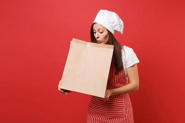 Femme au foyer femme chef cuisinier boulanger en tablier rayé t-shirt toque chapeau de chef isolé sur fond de mur rouge