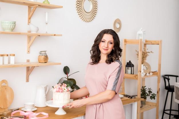 Une femme au foyer une femme pâtissière dans la cuisine a préparé un gâteau et un dessert sucré