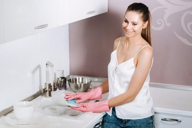 Femme au foyer fille en gants roses lave la vaisselle à la main dans l'évier avec un détergent