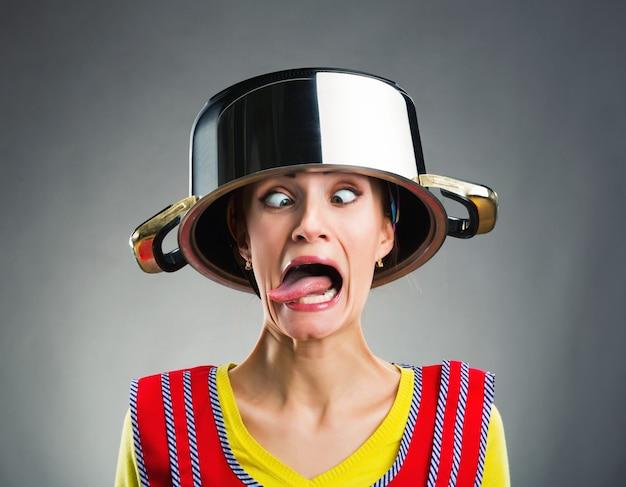 Femme au foyer folle avec une casserole de saucisse sur la tête
