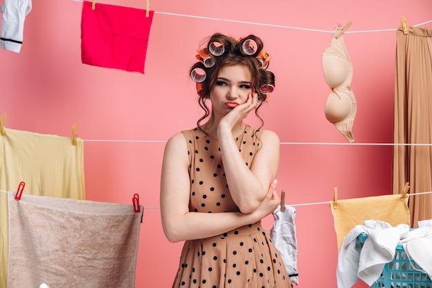 Femme au foyer sur fond rose montre qu'elle est fatiguée des travaux ménagers. corde avec des vêtements sur fond rose.
