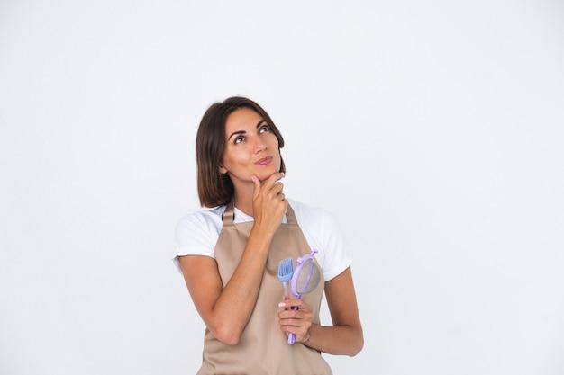 Femme au foyer heureuse en tablier isolé sur blanc réfléchie réfléchir à la recette quoi faire