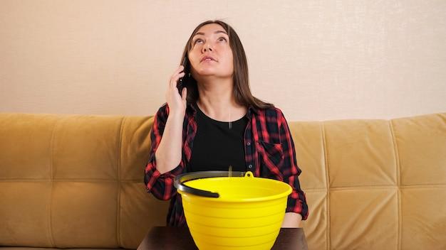 Une femme au foyer inquiète en chemise à carreaux appelle un plombier pour collecter de l'eau qui descend des voisins du dessus dans un seau jaune sur un canapé dans le salon
