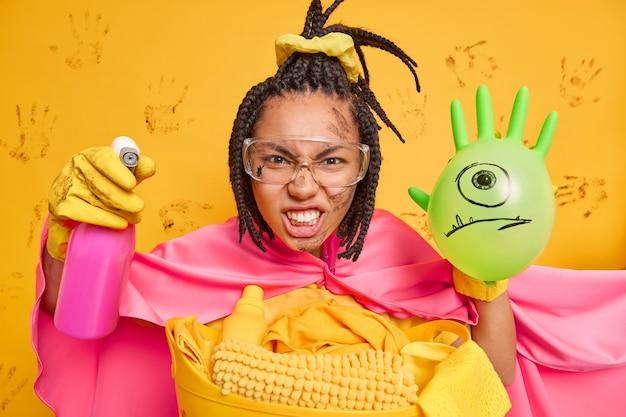 Une femme au foyer irritée tient un détergent de nettoyage et un ballon gonflé serre les dents de l'agacement porte des poses de costumes de super-héros près d'un panier à linge contre un mur jaune sale