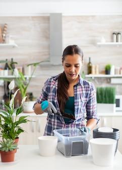 Femme au foyer jardinant dans la cuisine à la maison à l'aide de gants et d'une pelle