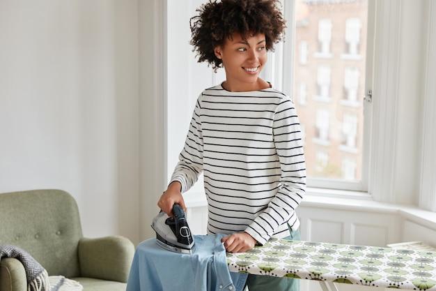 Femme au foyer joyeuse fait le ménage à la maison