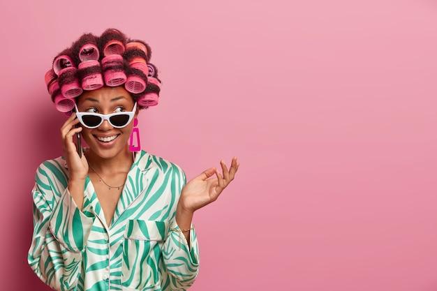 Une femme au foyer joyeuse et hésitante parle au téléphone, écoute les rumeurs et obtient une offre agréable porte des bigoudis, des lunettes de soleil et une robe de chambre, regarde joyeusement de côté pose sur un espace vide sur un mur rose