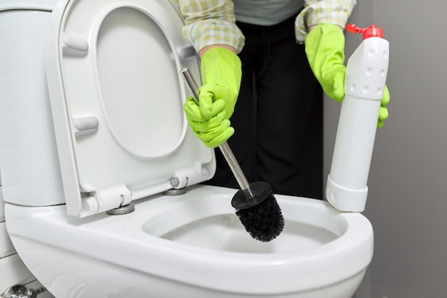 Femme au foyer lavant et désinfectant les toilettes. femme en gants avec détergent et brosse. ménage, propreté à la maison, tâches ménagères, service, concept de personnes