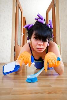 Femme au foyer lave un étage dans la maison