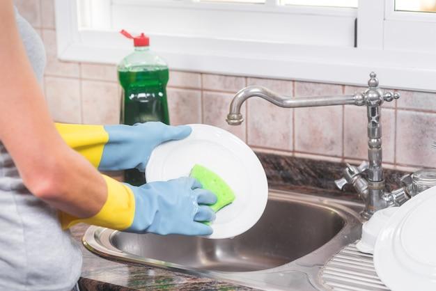 Femme au foyer lave la vaisselle dans la cuisine