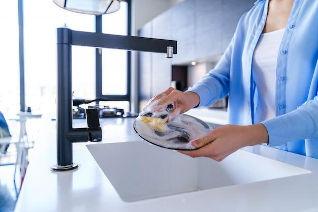 Femme au foyer lave la vaisselle sale après le dîner avec un détergent et une éponge